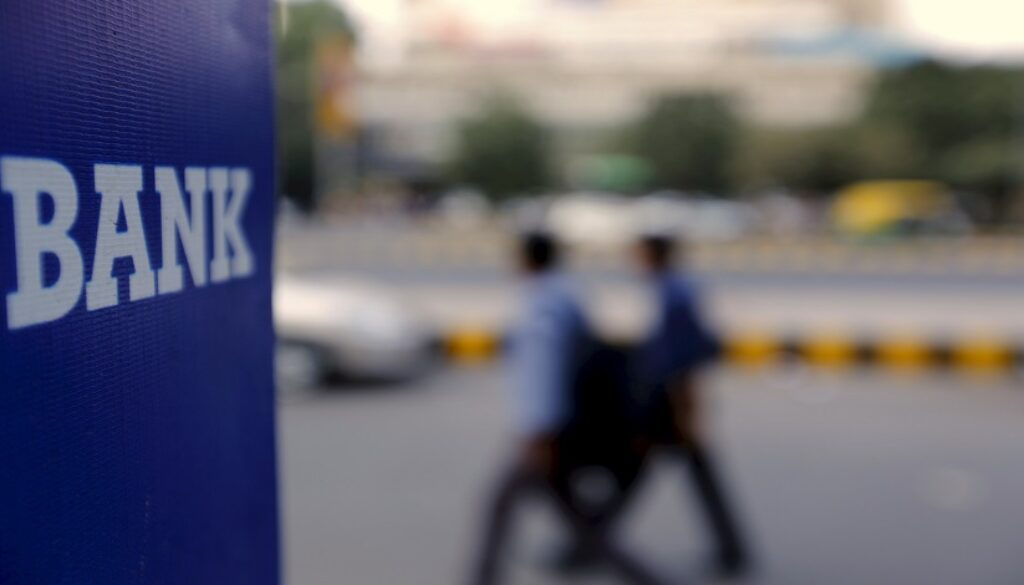File photo of commuters walking past a bank sign along a road in New Delhi